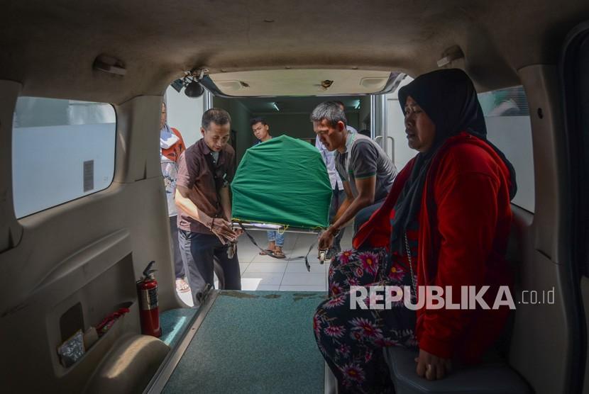 Keluarga membawa jenazah korban meninggal akibat keracunan minuman keras (miras) oplosan ke dalam mobil ambulans di Rumah Sakit Umum Daerah (RSUD) Cicalengka, Kabupaten Bandung, Jawa Barat, Senin (9/4).