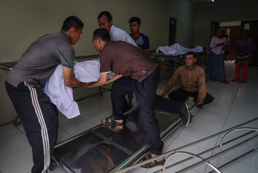 Keluarga memindahkan jenazah korban meninggal akibat keracunan minuman keras (miras) oplosan ke dalam mobil ambulans di Rumah Sakit Umum Daerah (RSUD) Cicalengka, Kabupaten Bandung, Jawa Barat, Senin (9/4).