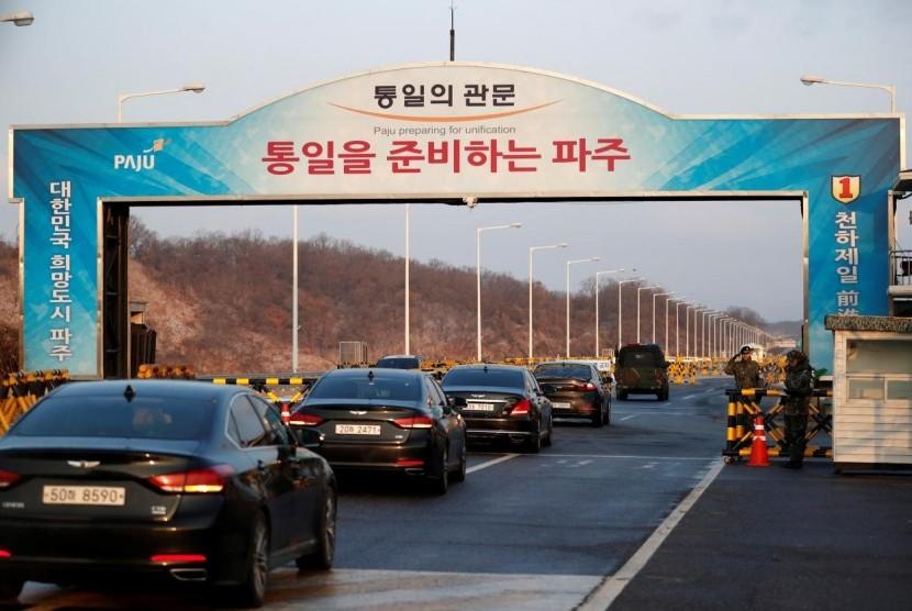 Kendaraan delegasi Korea Selatan yang dipimpin Menteri Unifikasi Korsel Cho Myoung-gyon melewati pos pemeriksaan di Jembatan Unifikasi Agung yang menuju ke Panmunjom di selatan zona demiliterisasi di Paju, Korsel, Selasa (9/1).