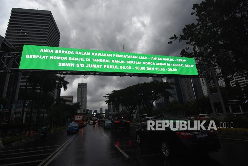Kendaraan melintas di dekat papan informasi kebijakan sistem pembatasan kendaraan bermotor berdasarkan nomor plat ganjil-genap di kawasan Sudirman, Jakarta, Kamis (21/3/2019).