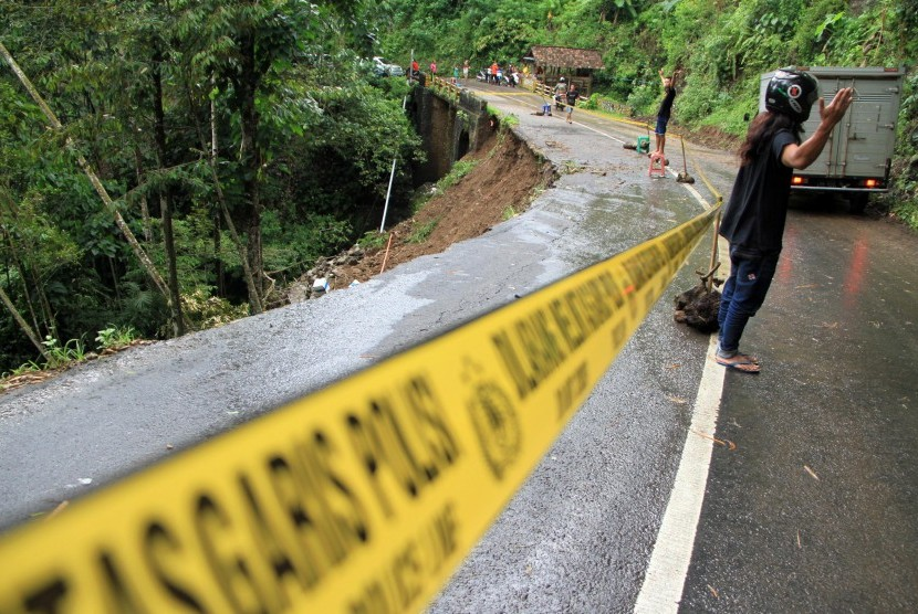 Kendaraan melintas di jalan nasional yang longsor di Desa Sawahan, Trenggalek, Jawa Timur, Jumat (9/9).