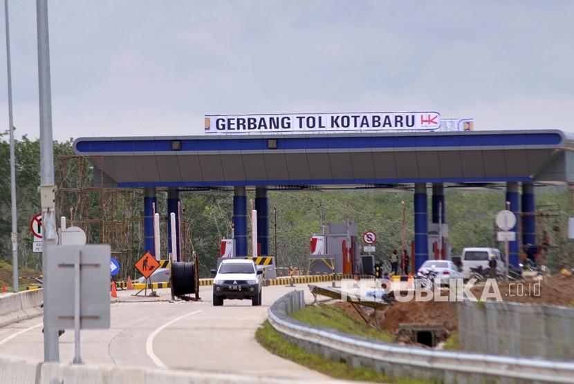 Kendaraan melintas di lokasi pembangunan pintu keluar Jalan Tol Trans Sumatera (JTTS) Seksi II Ruas Sidomulyo-Kota Baru di Desa Sabah Balau, Lampung Selatan, Lampung, Senin (18/12).