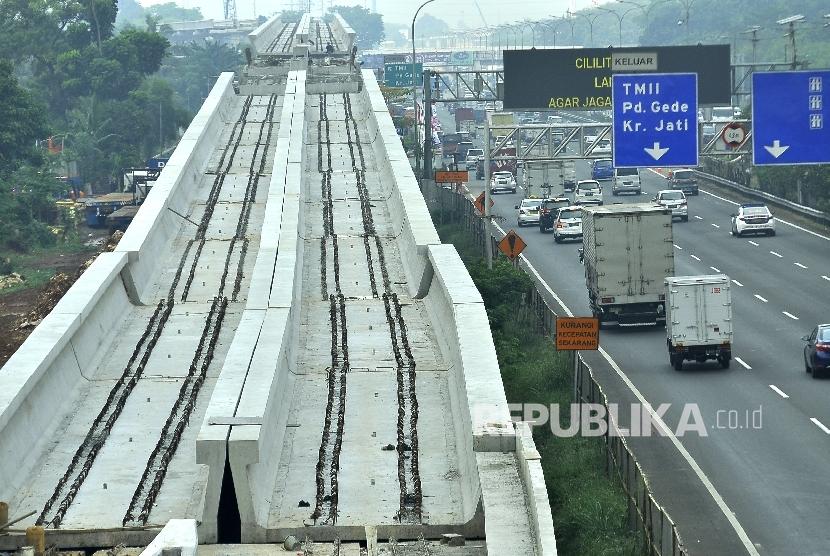 Kendaraan melintas di samping pembangunan proyek kereta ringan atau Light Rail Transit (LRT) rute Cibubur-Cawang di Tol Jagorawi, Kampung Makasar, Jakarta, Kamis (10/8).