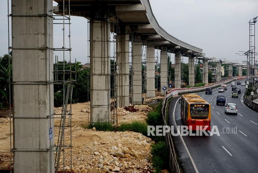 Kendaraan melintas di samping proyek infrastruktur transportasi massal kereta ringan atau Light Rail Transit (LRT) di kawasan Halim, Jakarta, Jumat (30/6).