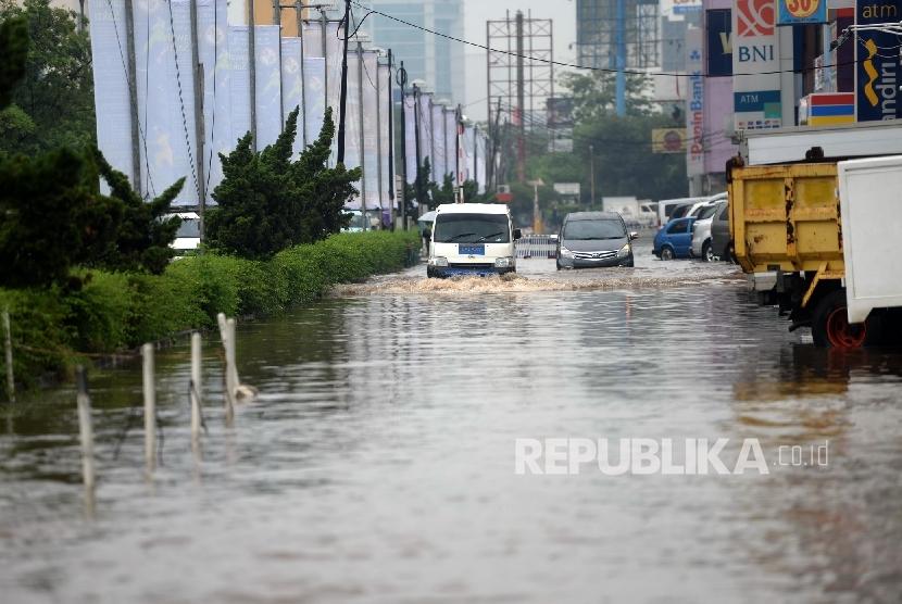 Kendaraan melintasi banjir di Kawasan Kelapa Gading, Jakarta Utara, Jumat (26/2).  (Republika/Wihdan)