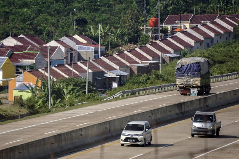 Kendaraan melintasi Jalan Tol Batang berlatar belakang kawasan rumah subsidi di Kabupaten Batang, Jawa Tengah, Jumat (18/6). BI juga melanjutkan pelonggaran rasio Loan to Value (LTV) atau Financing to Value (FTV) Kredit atau Pembiayaan Properti menjadi paling tinggi 100 persen.
