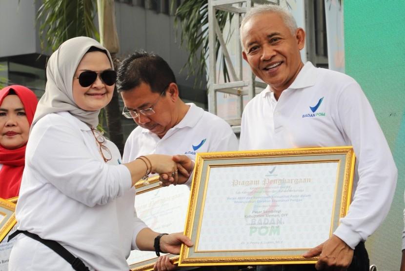 Kepala BPOM RI, Penny K Lukito, menyerahkan penghargaan pasar aman dari bahan berbahaya kepada Pasar Sambilegi yang diterima Bupati Sleman, Sri Purnomo.