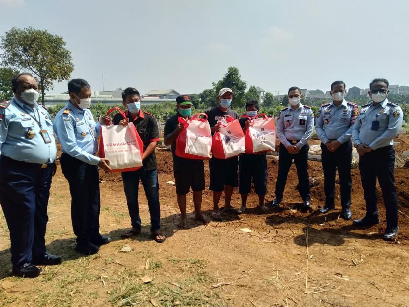 Kepala Kantor Wilayah Hukum dan HAM Jawa Barat Sudjonggo memberikan paket bantuan kepada penggali kubur TPU Pondok Rajeg yang berada di sekitaran Lapas Cibinong, Kabupaten Bogor, Kamis (29/7).
