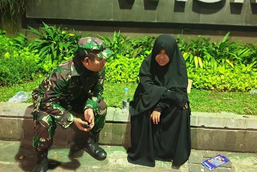 Kepala Urusan Operasional (Kaurops) Kodim Jakarta Pusat, Kapten Arm Sucita Sesko Wardana, membujuk wanita bercadar yang melakukan aksi menarik perhatian saat demonstrasi aksi 22 Mei di Jakarta pada 22 Mei.