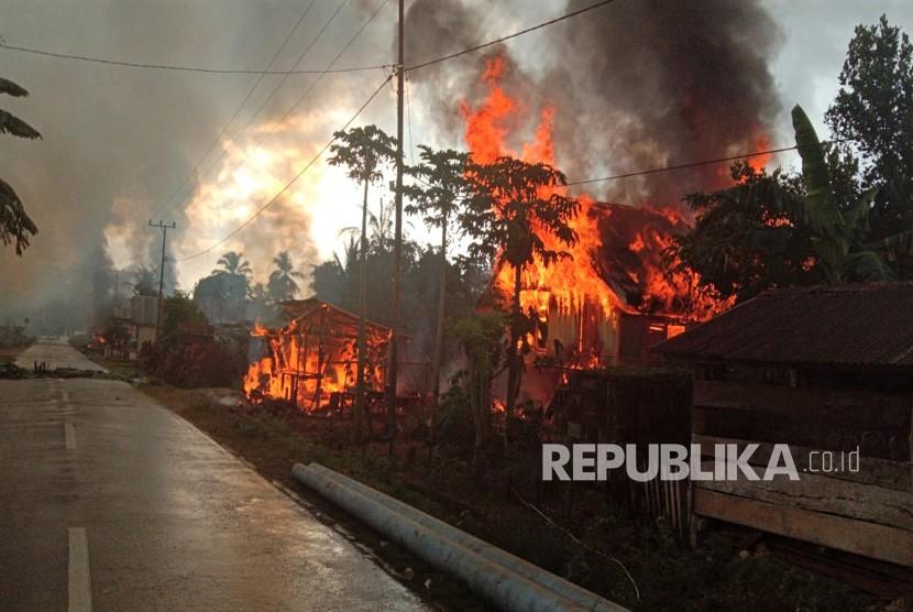 Kepulan asap hitam dari puluhan rumah yang dibakar di Desa Gunung Jaya usai terjadi keributan antar pemuda di perbatasan antara Desa Gunung Jaya dan Desa Sampuabalo, Buton, Sulawesi Tenggara, Rabu (5/6/2019).