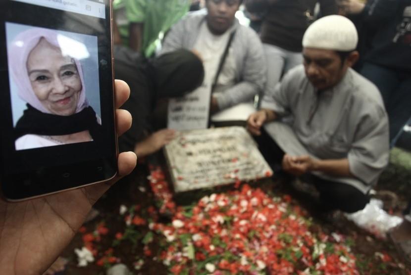 Kerabat berdoa di pusaran makam Penyanyi Laila Sari di TPU Karet Bivak, Jakarta, Selasa (21/11).