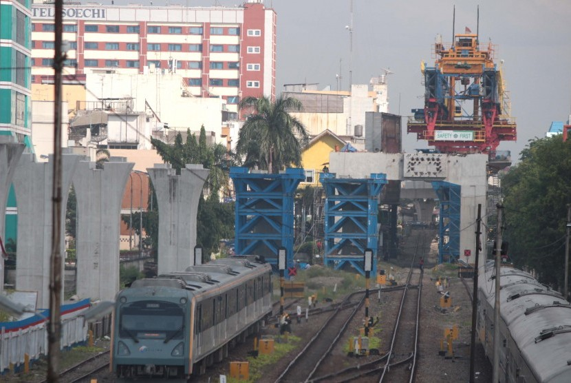 Kereta api bandara melintas di samping proyek pembangunan rel layang di Stasiun Besar Medan, Sumatra Utara.