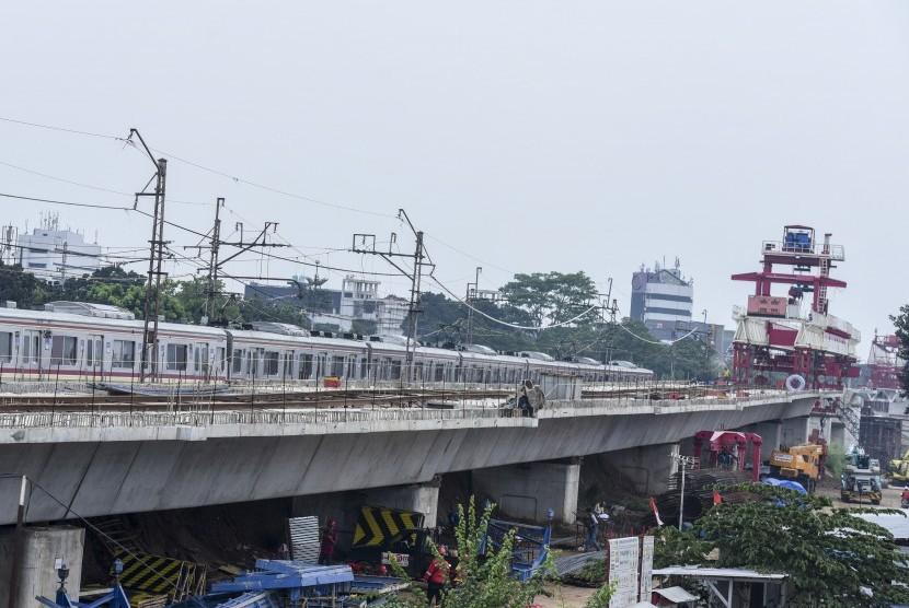 Kereta Rel Listrik (KRL) Commuter Line melintas di dekat proyek pembangunan jalur kereta dwi ganda (DDT) di kawasan Manggarai, Jakarta, Selasa (31/10).