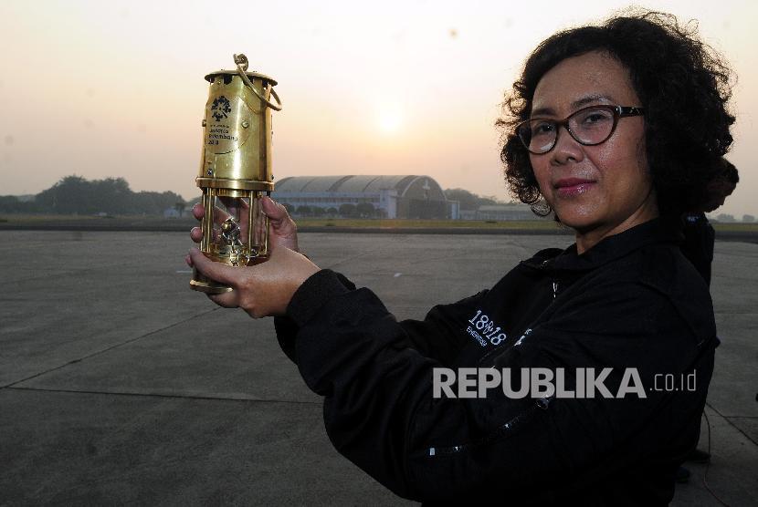 Ketua Delegasi Api Obor Celerina Judisari memperlihatkan alat untuk membawa api obor Asian Games 2018 usai acara pelepasan tim torch relay di Lanud AU Halim Perdana Kusuma, Jakarta, Sabtu (14/7).