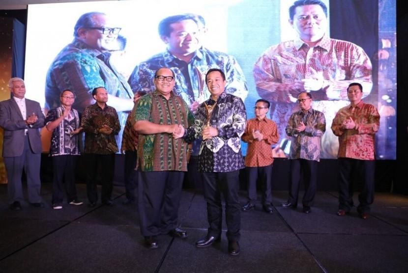 Ketua Dewan Juri Soegiharto (kiri) saat menyerahkan penghargaan Best of The Best BUMN Revolusi Mental BUMN Award 2018 kepada VP Human Capital Strategic Management Telkom Dharma Syahputra (kanan) di Jakarta, Rabu (25/8).