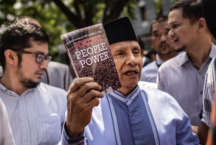 Ketua Dewan Kehormatan Partai Amanat Nasional (PAN) Amien Rais (tengah) menunjukkan buku berjudul Jokowi People Power saat jeda pemeriksaan untuk Shalat Jumat di Direktorat Reserse Kriminal Umum (Ditreskrimum) Polda Metro Jaya, Jakarta, Jumat (24/5/2019).
