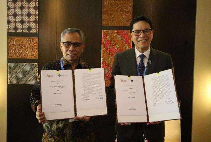 Ketua Dewan Komisioner OJK Wimboh Santoso dan Gubernur Bank of Thailand Veerathai Santiprabhob menandatangani nota kesepahaman perjanjian bidang perizinan, Jumat (12/10).