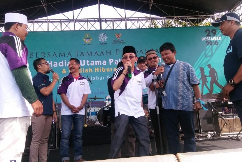 Ketua DKM Pusdai KH M Choirul Anam MZD (berpeci hitam) tengah mengumumkan pemenang undian paket perjalanan umrah dalam ajang Jalan Sehat Milad Pusdai ke-21 di Lapangan Gasibu, Kota Bandung, Sabtu (29/12).