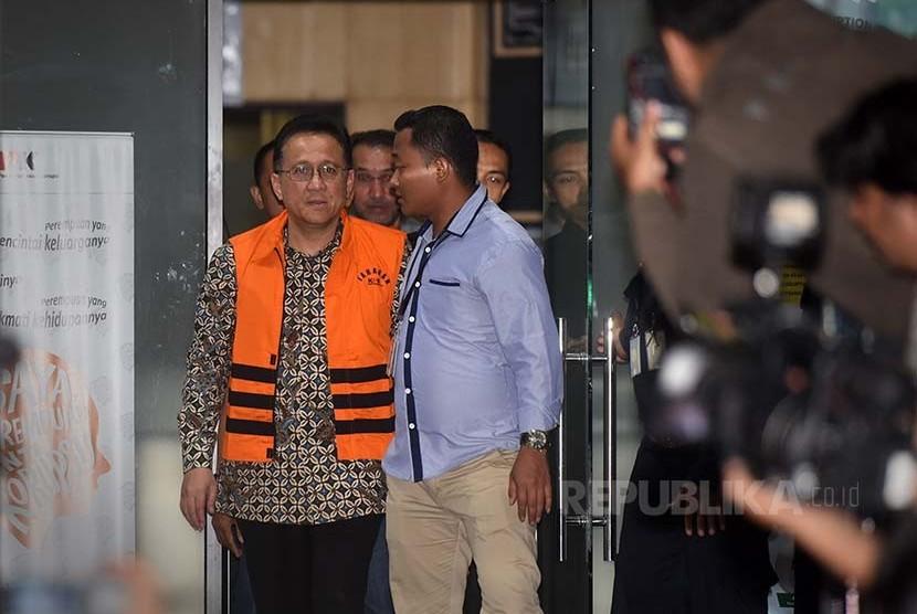 Ketua DPD Irman Gusman (kiri) keluar dari gedung KPK dengan mengenakan rompi tahanan KPK seusai diperiksa penyidik terkait kasus dugaan suap kuota impor gula, Jakarta, Sabtu (17/9)