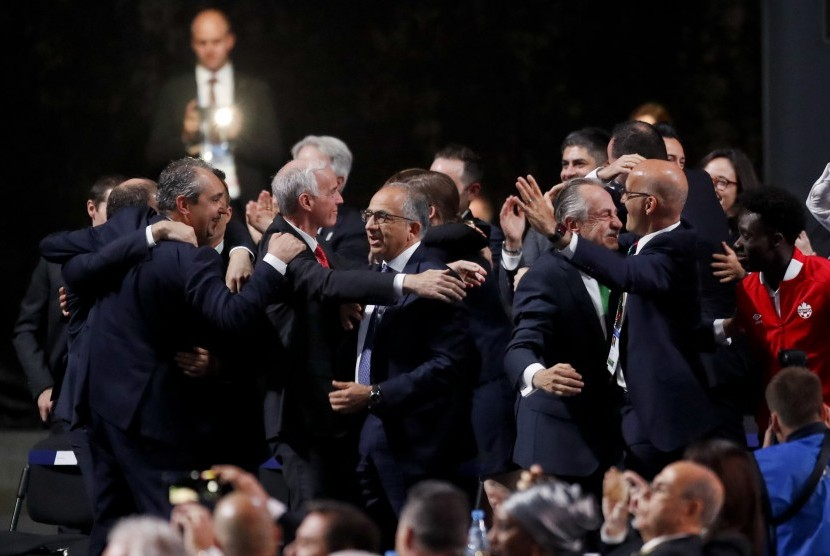 Ketua Federasi Sepak Bola Amerika Serikat, Carlos Cordeiro (tengah), memeluk rekannya dari Kanada, Steve Reed (dua kiri), setelah AS, Kanada, dan Mesiko terpilih sebagai tuan rumah bersama Piala Dunia 2026 di Kongres FIFA di Moskow, Rusia, Rabu (13/6).