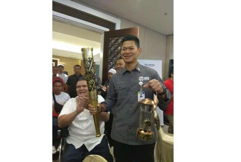 INAPGOC Chairman Raja Sapta Oktohari holds the 2018 Asian Para Games torch and lantern.