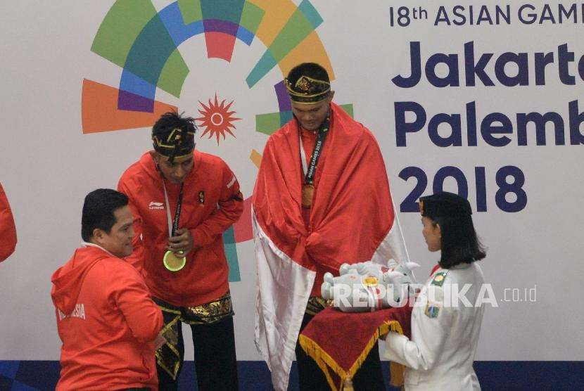 Ketua Inasgoc Erick Thohir mengalungkan medali kepada Pesilat Indoensia Yola Primadona Jampil dan Hendy pada final cabang pencak silat kelas artistik ganda putra Asian Games 2018 di Padepokan Pencak Silat TMII, Jakarta, Senin (27/8).