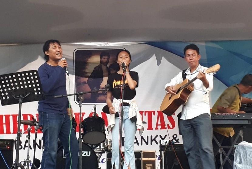Ketua Komunitas Tembang Balada Franky & Jane (TBF&J), Darul Farhan (kiri), bersama anggota TBF&J Vira dan Johnny Sahilatua (kanan) menyanyikan lagu karya Franky & Jane di Taman Mini Indonesia Indah, Jakarta Timur