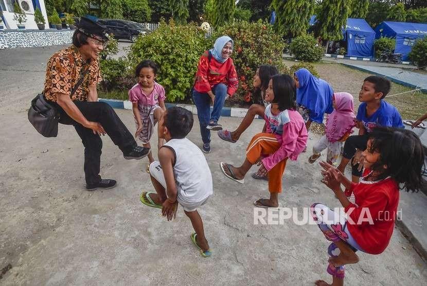 Ketua KPAI Seto Mulyadi atau Kak Seto melakukan Trauma Healing dengan cara mengajak bermain anak-anak korban gempa tsunami Palu di kantor Dinas Sosial, Palu, Sulawesi Tengah, Jumat (5/10).