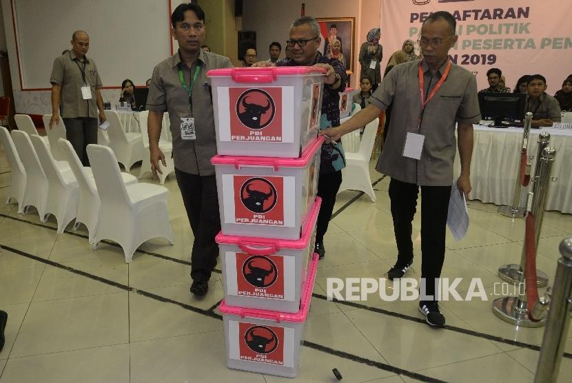 Ketua KPU Arief Budiman bersama petugas menata boks kontainer berisi berkas dan syarat pendaftaran partai PDI-P di kantor KPU Pusat, Jakarta, Rabu (11/10).