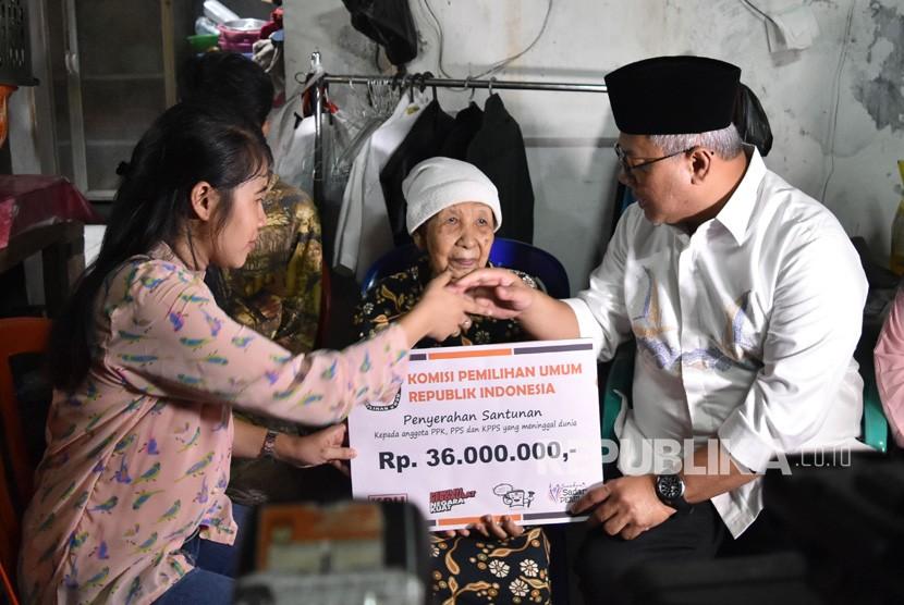Ketua KPU Arief Budiman (kanan) menyerahkan santunan kepada keluarga almarhum Tutung Suryadi, petugas KPPS yang wafat, di Tangki, Tamansari, Jakarta Barat, Jumat (3/5/2019).