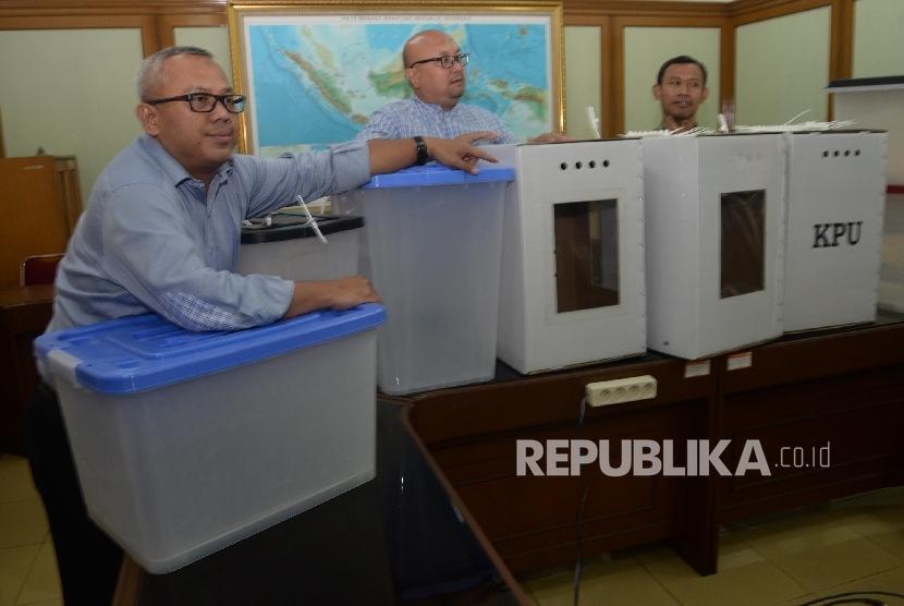 Ketua KPU Arief Budiman (kiri), bersama anggota KPU Pramono Ubaid Tanthowi (kanan), dan Ilham Saputra (tengah) menunjukkan contoh alternatif bentuk kotak suara transparan terbuat dari kertas karton dan Box plastik akan digunakan dalam Pilkada serentak 2018 dan Pemilu 2019 di kantor KPU, Jakarta, Senin (7/8).