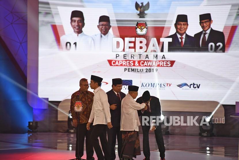 Ketua KPU Arief Budiman (kiri) bersama pasangan capres-cawapres nomor urut 01 Joko Widodo (kedua kiri) dan Ma'ruf Amin (kedua kanan) serta pasangan nomor urut 02 Prabowo Subianto (tengah) dan Sandiaga Uno (kanan) bersiap mengikuti debat pertama Pilpres 2019, di Hotel Bidakara, Jakarta, Kamis (17/1/2019).