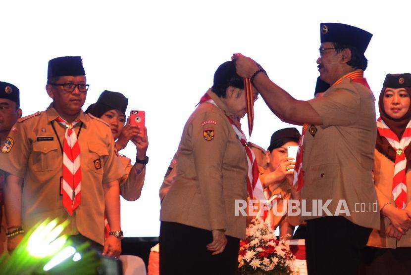 Ketua Kwartir Nasional (Kwarnas) Pramuka Adhyaksa Dault (kanan) menyematkan lencana Tunas Kencana kepada kepada Presiden ke-5 RI Megawati Soekarnoputri (tengah) saat Penutupan Jambore Nasional X 2016 di Bumi Perkemahan Cibubur, Jakarta Timur, Sabtu, (20/8)