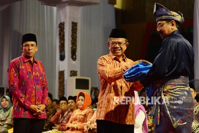 Ketua LPTQ Machasin (kedua kiri) memberikan bendera MTQ kepada PLT Gubernur Sumatera Utara Tengku Erry Nuradi (Kanan) disaksikan Gubernur Nusa Tenggara Barat TGH M. Zainul Majdi (kiri) saat menghadiri penutupan MTQ Nasional yang diadakan di Islamic Center