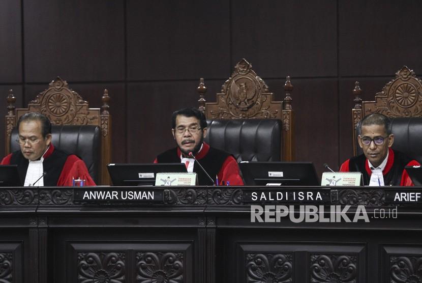 Ketua Majelis Hakim Mahkamah Konstitusi (MK) Anwar Usman (tengah) didampingi Majelis Hakim MK Saldi Isra (kanan) dan Aswanto (kiri) memimpin sidang pembacaan putusan di ruang sidang pleno Gedung MK, Jakarta, Senin (23/7).