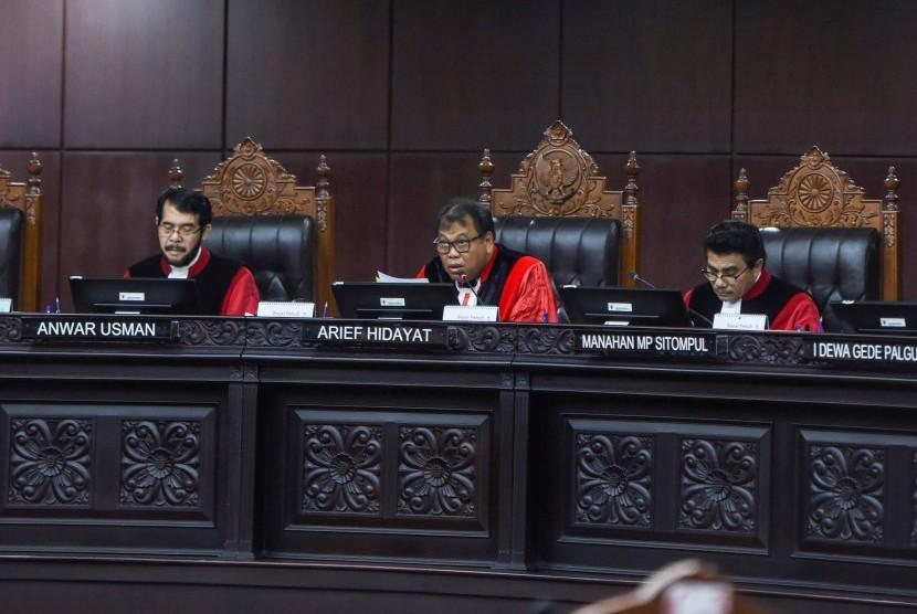 Ketua Majelis Hakim Mahkamah Konstitusi (MK) Arief Hidayat (tengah) didampingi Majelis Hakim MK Anwar Usman (kiri) dan Manahan MP Sitompul (kanan) memimpin sidang dengan agenda pembacaan putusan uji materi UU terkait pemberian remisi di Mahkamah Konstitusi, Jakarta, Selasa (7/11).