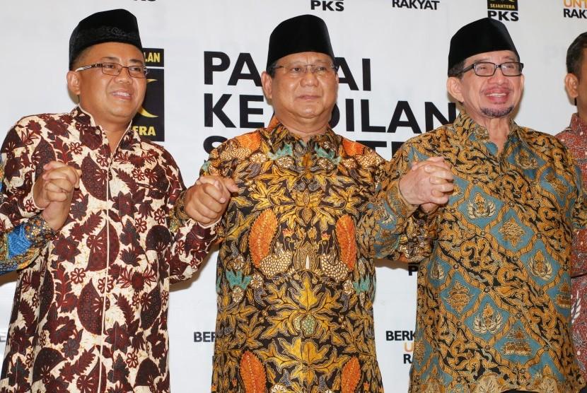 Ketua Umum Partai Gerindra Prabowo Subianto (tengah) bergandengan tangan dengan Presiden PKS Sohibul Iman (kiri) dan Ketua Majelis Syuro PKS Salim Segaf Aljufri (kanan) seusai melakukan pertemuan di DPP PKS, Jakarta, Senin (30/7).