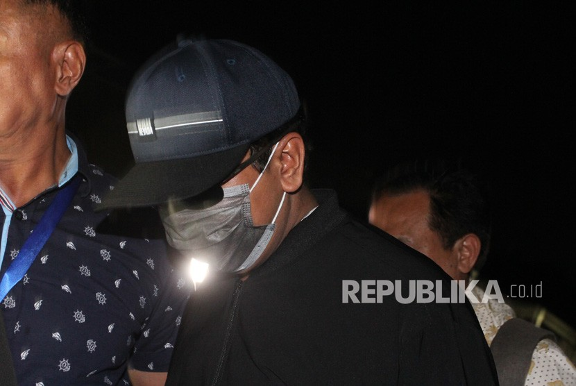 Ketua Umum Partai Persatuan Pembangunan (PPP) Romahurmuziy (mengenakan masker dan bertopi), digiring petugas saat tiba di Gedung KPK Merah Putih, Jakarta, Jumat (15/3/2019).