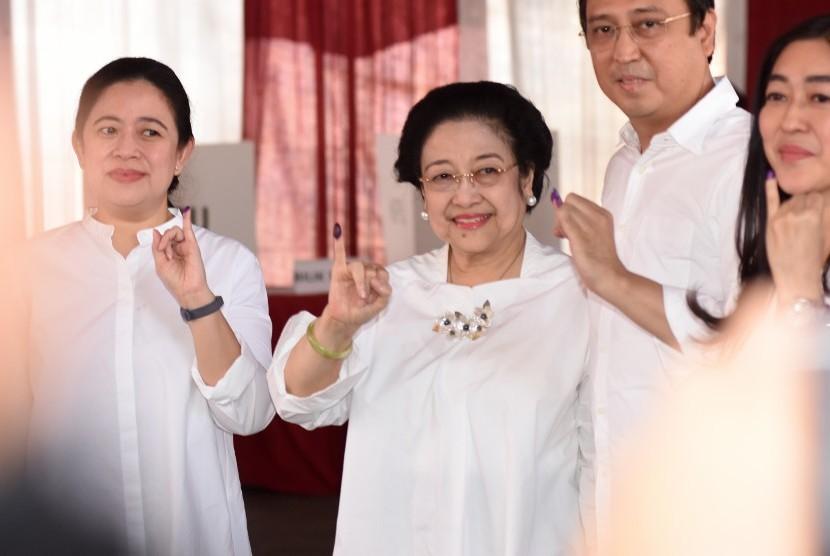 Ketua Umum PDI Perjuangan yang juga Presiden kelima RI Megawati Soekarnoputri (tengah) bersama putrinya Puan Maharani (kiri) dan putranya Muhammad Prananda Prabowo (kedua kanan) menunjukkan jarinya yang telah dicelup tinta seusai menggunakan hak pilihnya pada Pemilu 2019 di TPS 62, Kebagusan, Jakarta, Rabu (17/4/2019).