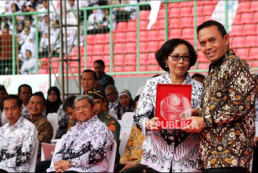 Ketua Umum PGRI Unifah Rosyidi (kedua kanan) memberikan penghargaan atas dedikasi peningkatan kompetensi guru kepada PT Telkom Indonesia yang diwakili oleh Direktur Human Capital Management PT Telkom Herdy Rosadi Harman (kanan) (Ilustrasi)