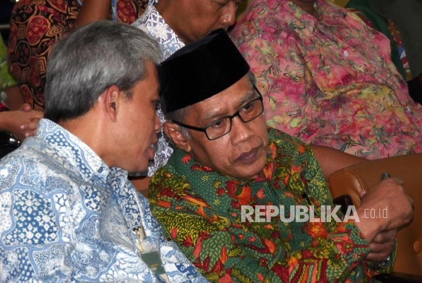 Ketua Umum PP Muhammadiyah Haedar Nashir (kanan) berbincang dengan Direktur Utama Bank Syariah Mandiri Agus Sudiarto usai menandatangani nota kesepakatan bersama di Jakarta, jumat (5/8).
