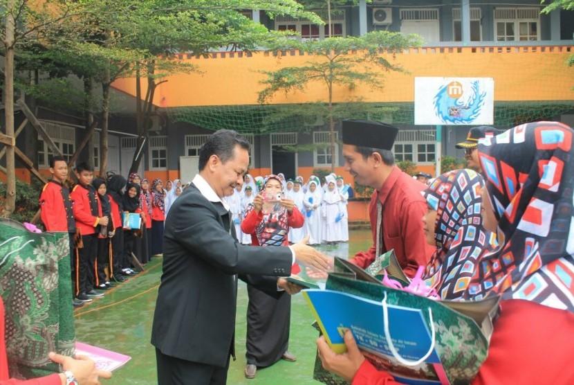Ketua Umum Yayasan Perguruan Al-Iman Afrizal Sinaro menyerahkan penghargaan kepada guru teladan.