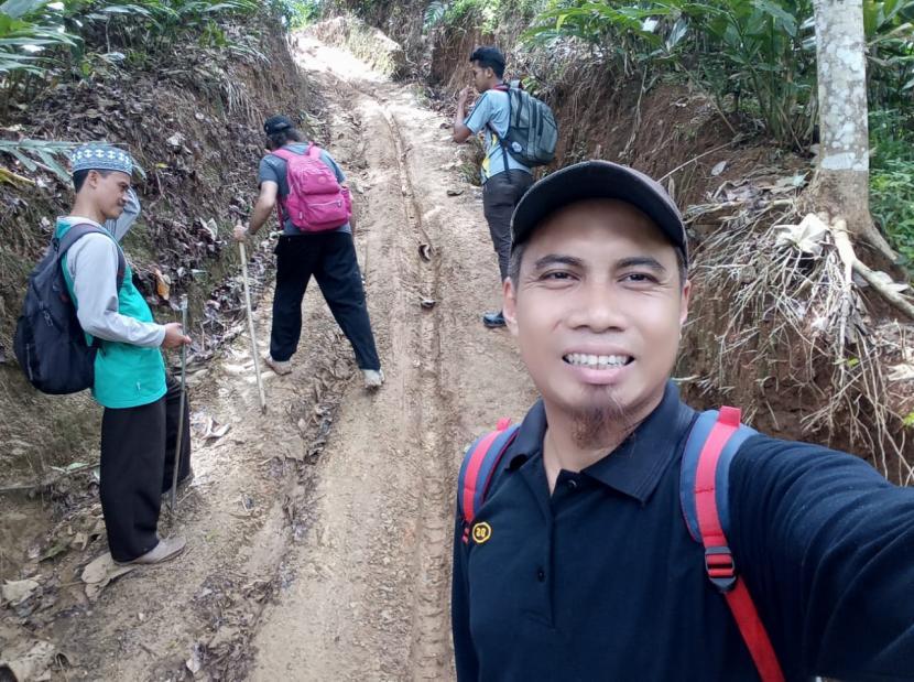 Ketua Yayasan Mukmin Kabupaten Kuningan, Ade Supriadi, saat mendaki jalur menuju Blok Pugag, Dusun Kujangsari, Desa Kutawaringin, Kabupaten Kuningan, untuk membina mualaf.