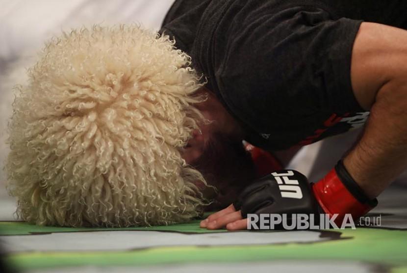 Khabib Nurmagomedov sujud syukur setelah mengalahkan Dustin Poirier pada laga perebutan gelar Kelas Ringan UFC Lightweight di Abu Dhabi, Uni Emirat Arab, Ahad (8/9) dini hari.