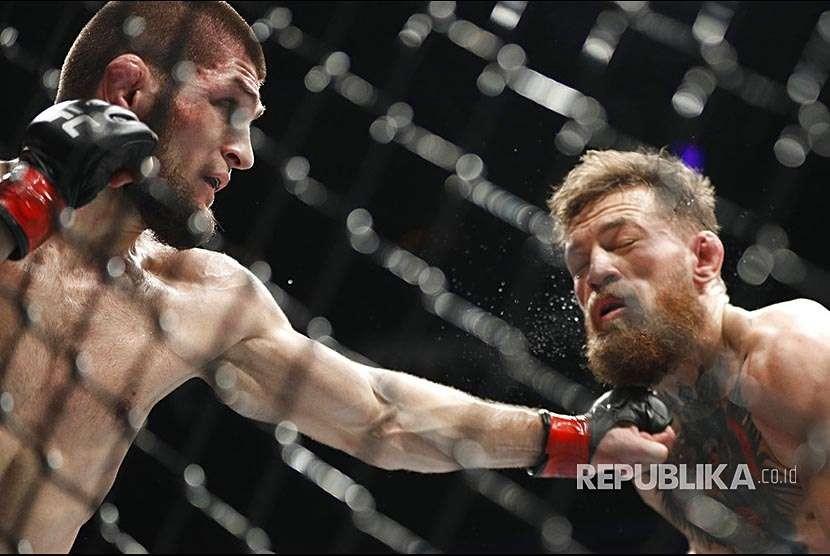 Khabib Nurmagomedov melepaskan pukulan ke arah wajah Conor McGregor pada laga UFC 229 di Las Vegas, Sabtu (8/10) waktu setempat.