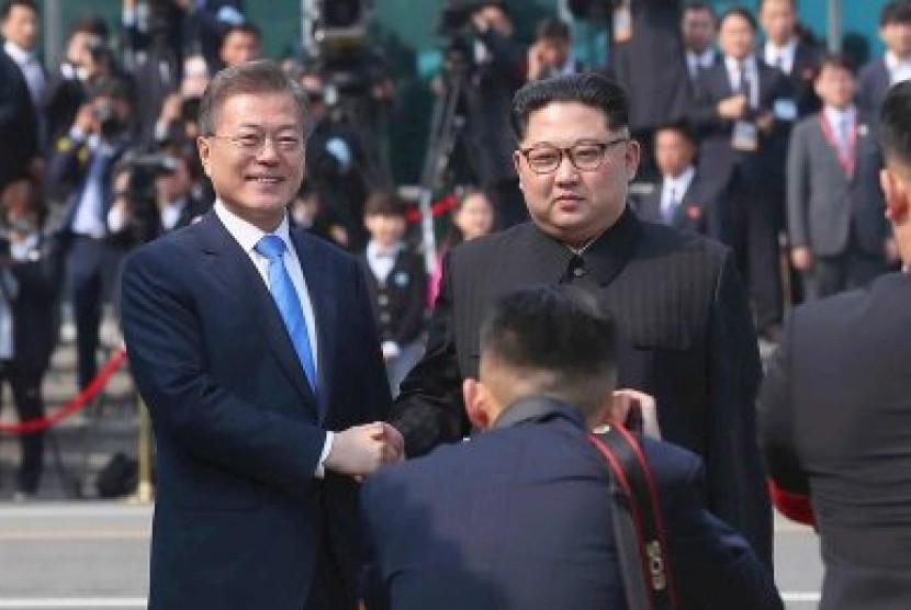 Kim Jong-un (kanan) berjabat tangan dengan Presiden Moon Jae-in.