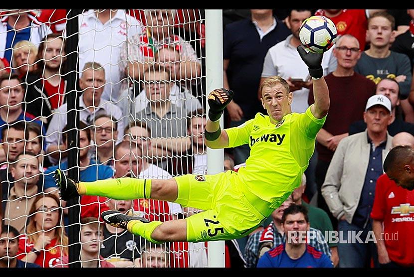 Kiper Westham United Joe Hart menghalau bola saat melawan tim Manchester United Paul Pogba di Stadion Old Trafford, Manchester, Ahad (13/8)