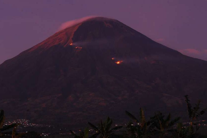 Kobaran api dan kepulan asap kebakaran hutan Gunung Sindoro terlihat dari Desa Muntung, Candiroto, Temanggung, Jawa Tengah, Senin (10/9).
