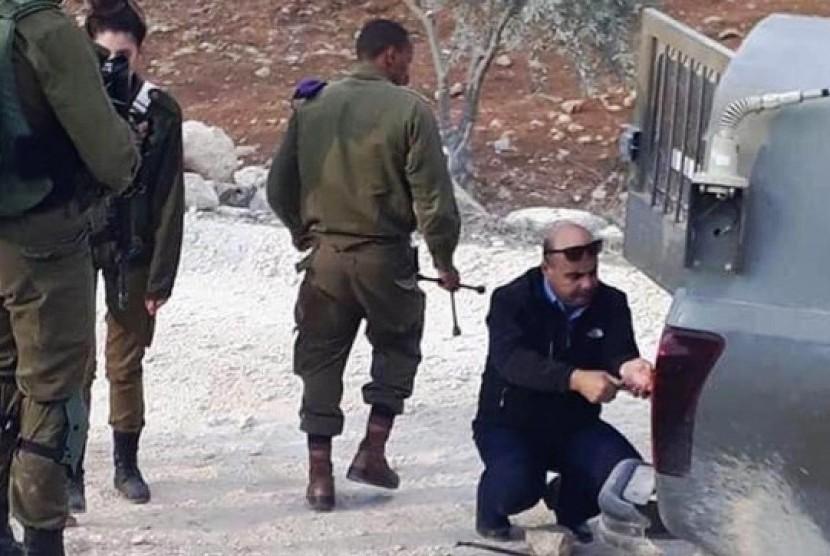 Kolonel Ahmad Abu ar-Rabb membantu polisi Israel memperbaiki kendaraan mereka.