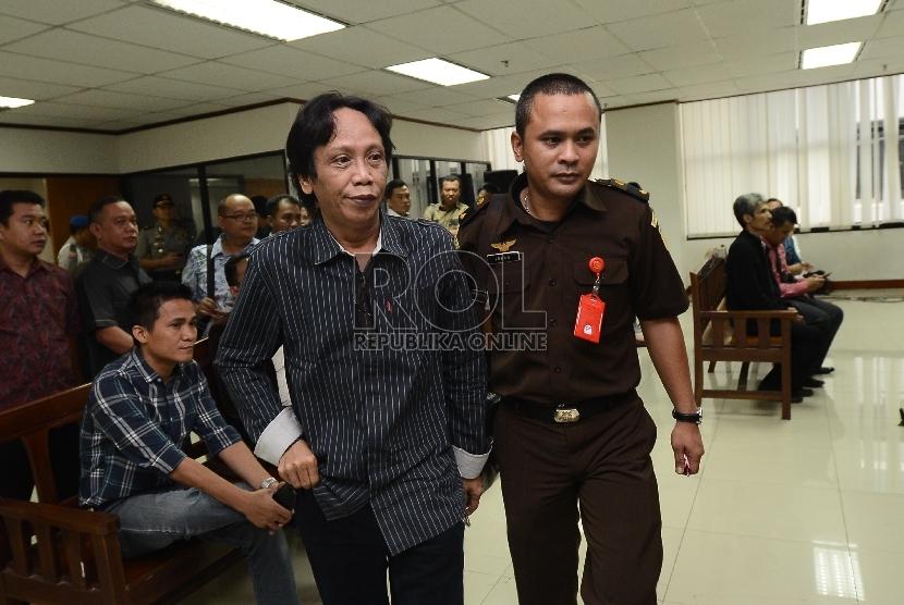 Komedian Betawi yang juga Direktur PT. Viandra Production Mandra Naih, berjalan menuju meja sidang untuk menyimak pembacaan dakwaan saat sidang di Pengadilan Tipikor, Jakarta, Kamis (20/8).